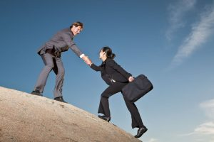 Two business people helping each other up a cliff.